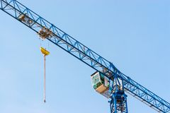 Industrial construction crane hoisting against blue sky.  Stock Photo