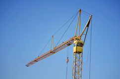 Industrial construction crane in the sky. Yellow Industrial construction crane on a blu background royalty free stock photo