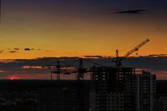 Industrial construction cranes on amazing sunset sky background. Crane,Construction tower crane equipment over building construction site silhouette,Industrial stock photography