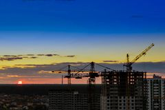Industrial construction cranes on amazing sunset sky background. Crane,Construction tower crane equipment over building construction site silhouette,Industrial royalty free stock photo