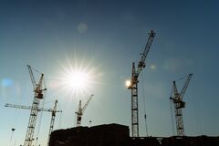 Free Industrial Construction Cranes And Building Silhouettes Over Sun At Sunrise Or Sunset. Stock Photo - 190964690