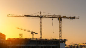 Industrial construction cranes and building silhouettes. Before sunset in construction site Stock Photography