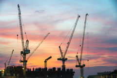 Industrial construction cranes and building silhouettes over sun Royalty Free Stock Images