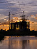Industrial construction cranes and building silhouettes. Over sun at sunrise Stock Image