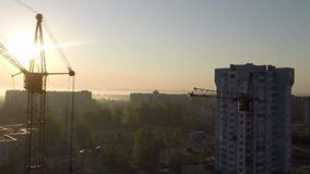 Industrial construction cranes and building silhouettes over sun at sunrise stock footage