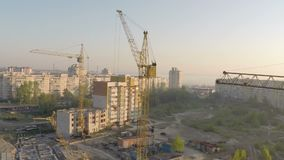Industrial construction cranes and building silhouettes over sun at sunrise stock video footage