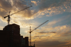 Industrial construction cranes and building silhouettes over sun at sunrise. Royalty Free Stock Photo
