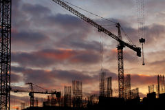 Industrial construction cranes and building silhouettes over sun at sunrise. Stock Images