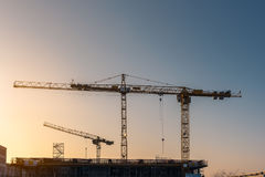 Industrial construction cranes and building silhouettes. Before sunset in construction site Royalty Free Stock Images