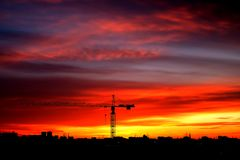 Industrial construction cranes and building silhouettes at sunse royalty free stock images