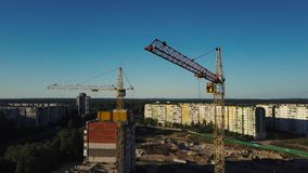 Industrial construction cranes and buildings over sun at sunset stock video