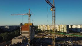 Industrial construction cranes and buildings over sun at sunset stock footage