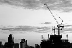 Industrial construction cranes and city. Silhouette over sunrise.Processed in black and white royalty free stock image