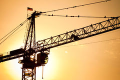 Industrial construction cranes over sun Stock Photo