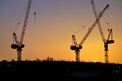 Industrial construction cranes silhouettes. sunset Stock Images