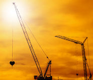 Industrial construction cranes. Silhouettes sunset Stock Photos