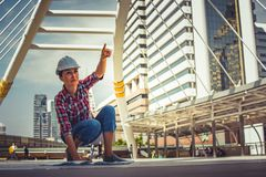 Industrial construction engineer wear safety helmet engineering working and drawings inspection on building outside. Engineering tools and construction concept royalty free stock images