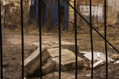 Industrial construction garbage behind the metal fence. Industrial construction garbage behind the fence Stock Image