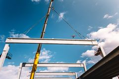 Industrial construction site with tower crane working with prefabricated beams and pillars stock photo