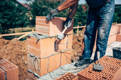 Industrial construction worker, professional bricklayer worker placing bricks on cement while building exterior walls Stock Photos