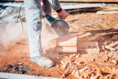 Industrial construction worker using a professional angle grinder. Industrial construction worker using an angle grinder Royalty Free Stock Image