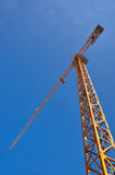 Industrial crane. Low angle view of tall industrial crane with blue sky background and copy space Royalty Free Stock Image