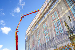 Industrial crane casting concrete on building top Stock Photo