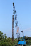 Industrial crane by forest Stock Images