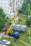 Industrial crane lift up container box to load it onboard truck. Crane raising container to load it in truck in city yard stock images