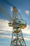 Industrial crane. Old industrial crane towards blue sky and clouds royalty free stock photo