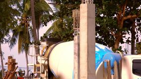 Industrial Crane operating and lifting cement tank stock video