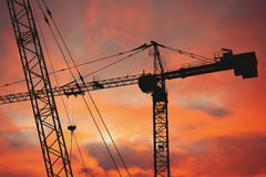 Industrial crane silhouettes over sunset. Royalty Free Stock Photos