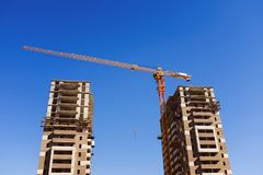 Industrial crane and unfinished multi-storey brick concrete building on the construction site against the sky. The concept of long stock images