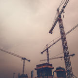 Industrial Cranes on Construction Site, Retro Toned Royalty Free Stock Images