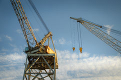Industrial cranes. Old industrial cranes towards blue sky and clouds stock images