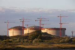 Industrial cranes and storage tanks Royalty Free Stock Image