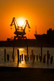 Industrial Cranes at Sunset. A pair of cargo cranes sit at rest in a industrial shipyard at sunset Stock Photography