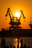Industrial Cranes at Sunset. A pair of cargo cranes sit at rest in a industrial shipyard at sunset Royalty Free Stock Photos