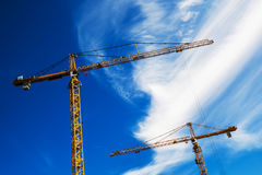 Industrial Cranes Working on Construction Site. Against Blue Sky Stock Image