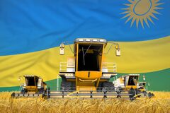 Four orange combine harvesters on grain field with flag background, Rwanda agriculture concept - industrial 3D illustration