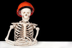 Industrial death. A skeleton with hard hat symbolizes death to the building industry royalty free stock image