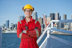Industrial deck hand. Docker and deck hand posing on the bridge of a ship, about to moor off in a city harbor, with the seattle skyline in the background Royalty Free Stock Photos
