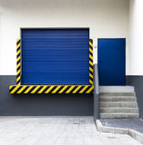 Industrial delivery gate. Blue shuttered industrial delivery gate and warning sign on building exterior Royalty Free Stock Photo