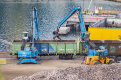 Industrial diggers load railway carriages. In Odessa Marine Trade Port. Odessa, Ukraine - August 22, 2016 Stock Photography