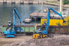 Industrial diggers and railway carriages. In Odessa Marine Trade Port. Odessa, Ukraine - August 22, 2016 Stock Images