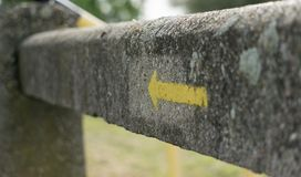 Yellow sign. Industrial direction indicator on concrete fence Royalty Free Stock Photos
