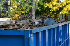 Industrial dumpster filled with debris. Industrial dumpster filled Loaded dumpster near a construction site, home renovation Stock Photography