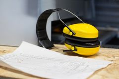 Industrial earmuffs and bill on table at workshop Stock Photography