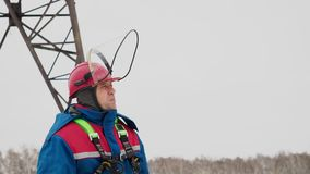 Industrial electrical station and professional electrician man. In helmet and overalls work on the power line, going on the field to electricity tower for stock video footage
