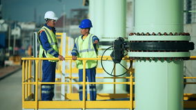 Industrial engineer and worker discussing in factory stock footage